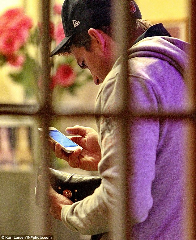 A minor distraction: Ashton seemed fixated on his cell phone at one point