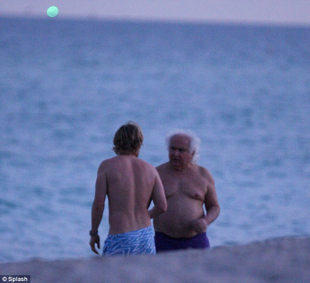 Catching up: Owen seemed to bump into a pal as he wandered down the beach following his dip in the ocean