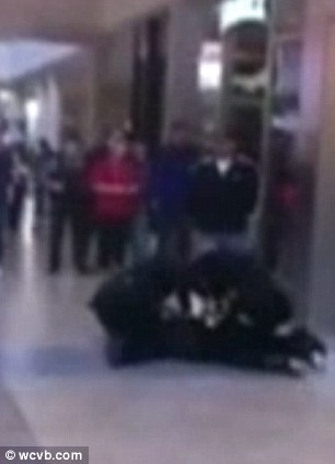 Struggle: Li is seen lying on the ground as she is tased by policemen on either side of her