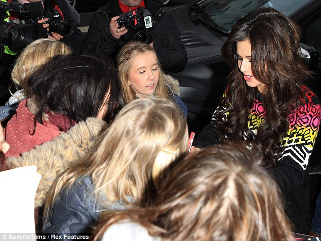 Greeting fans: Cheryl happily signed autographs for her eager waiting devotees