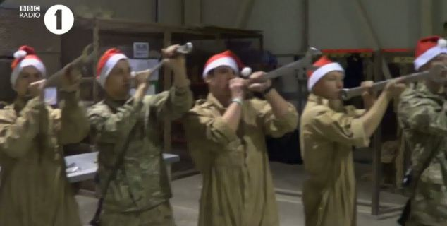 Party mood: Engineers pretend to be part of the band playing along to the Christmas hit