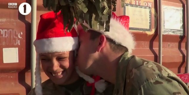 Cheeky: A soldier grabs a quick kiss while the pair are briefly under the mistletoe