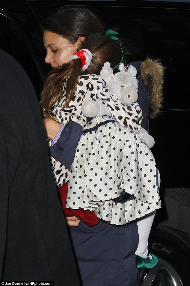 Tuckered out: Sleepy Suri Cruise cuddles up to her mother Katie Holmes as they head to a play date in New York on Friday