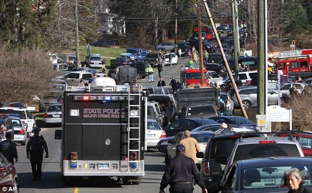 Tragedy: The scene outside the Sandy Hook Elementary School, where 28 people were killed
