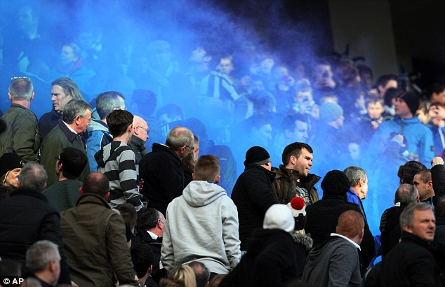 Sea of blue: City fans lit a flare during the match