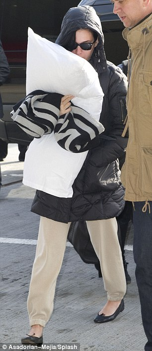 Tight fit: After shedding her puffy overcoat and flats for the TSA, a barefoot Katy wore sweats that hugged her derriere in all the wrong ways