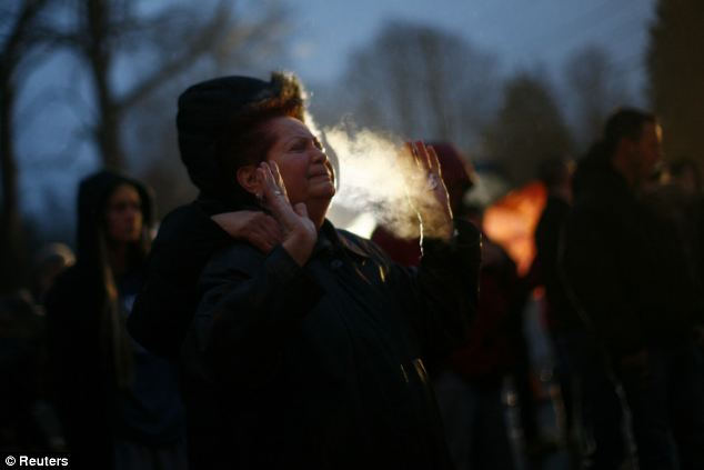 Grief: A woman cries at a makeshift memorial near Sandy Hook Elementary School