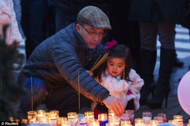 Remembrance: A mourner places joss sticks at a memorial for victims
