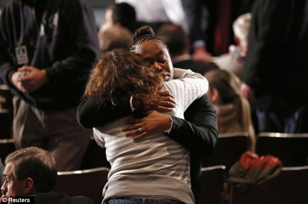 Support: Women embrace at a vigil held at Newtown High School for families of the Sandy Hook Elementary School shooting victims