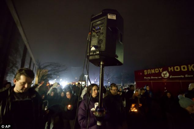 Attention: Mourners listen to a memorial service over a loudspeaker outside Newtown High School