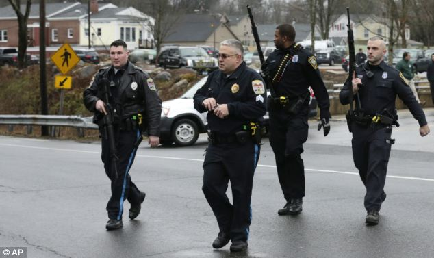 Lockdown: Police officers cross the road after searching a strip mall near an elementary school, which was in a lockdown, in Ridgefield