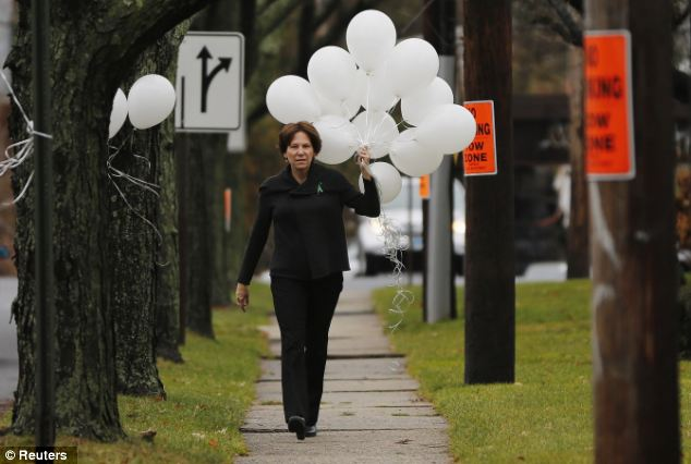 Marked: A woman carries balloons to the Abraham L. Green & Sons Funeral Home, where Sandy Hook Elementary school victim Noah Pozner's funeral will be held