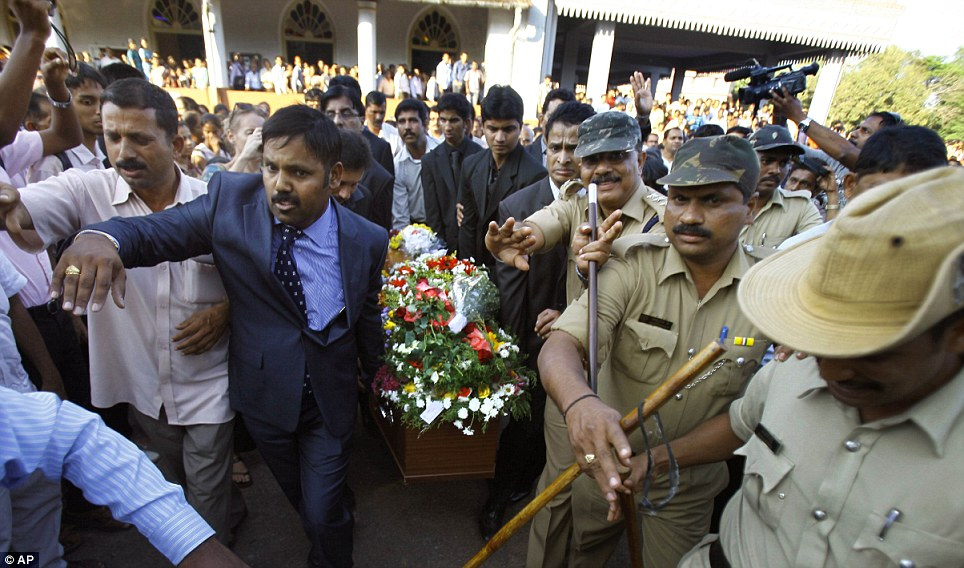 Moving back: Indian policemen try to control the crowd as relatives carry the coffin containing the body of nurse Jacintha Saldanha for burial at her hometown Shirva