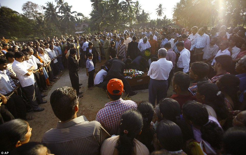 Wide angle: Relatives and friends gather during the burial of nurse Ms Saldanha at her hometown Shirva