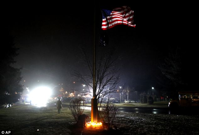 Poignant: A young boy places a candle with others at the base of a flagpole outside Newtown High School before the interfaith vigil