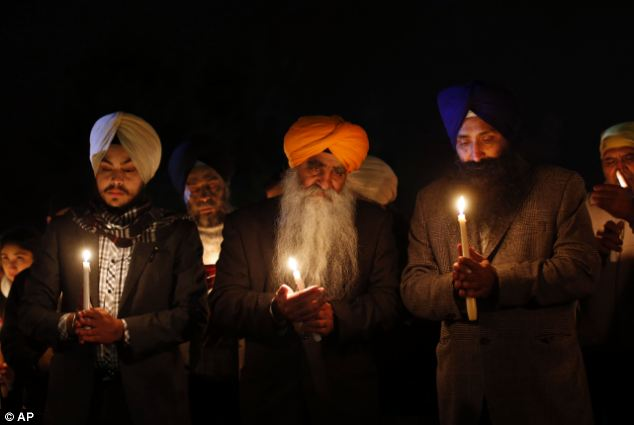 United: Members of the Sikh community hold a candlelight vigil outside Newtown High School