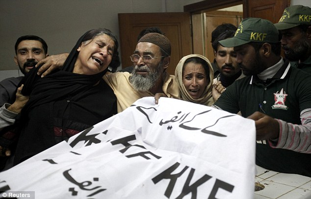 Amtiaz Khan, centre, brother of Nasima Bibi, comforts other relatives next to Nasima's covered body at a hospital morgue in Karachi