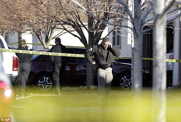 Tragic investigation: Police work behind a cordon of crime scene tape wrapped around a Colorado home where an apparent triple-murder suicide took place early this morning