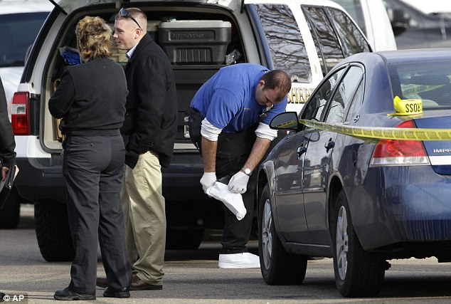 Questions: A man places white covers over his shoes while investigating the scene that has so far left its victims unidentified and a motive not known