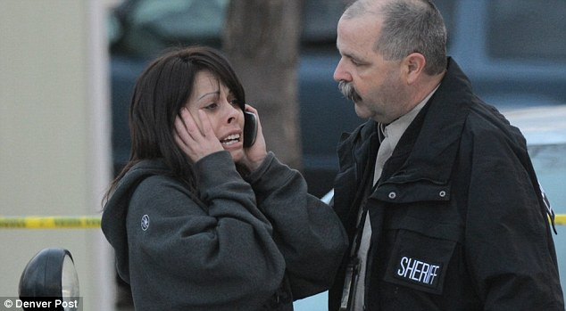 A devastated woman reacts to news of the shooting early this morning in a suburb outside Denver Colorado