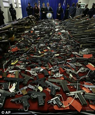 Gun and done: Guns cover tables in front of New Jersey Attorney General Jeffrey Chiesa, center, in Camden