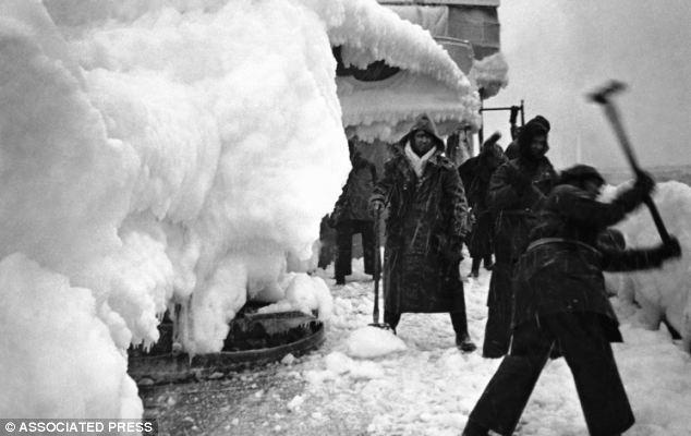 Frozen hell: Sailors chipping away the ice and snow from the deck of H.M.S. Vansittart while on convoy escort duty in the Arctic in February 1943