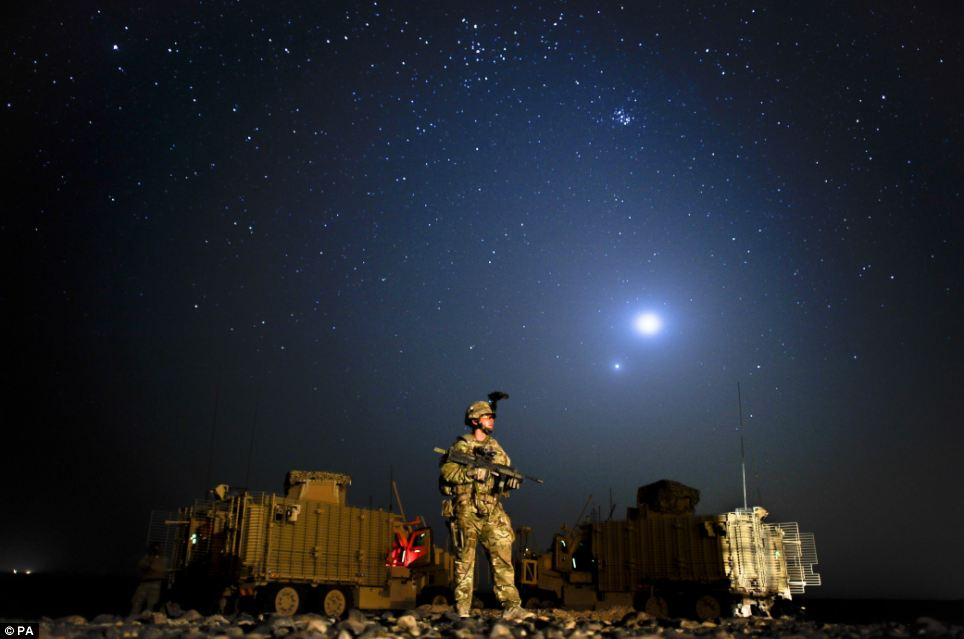 Starry night: Sergeant Jon Van Zyl of the Princess of Wales's Royal Regiment stands in front of two Mastiff vehicles and beneath Venus and Jupiter in Helmand desert, Afghanistan