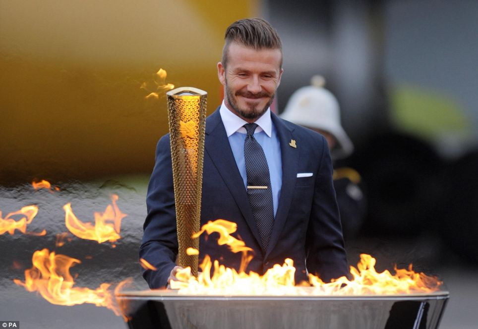 Here it comes: David Beckham with the torch during the ceremony to mark the arrival of the Olympic flame, at RNAS Culdrose, Cornwall