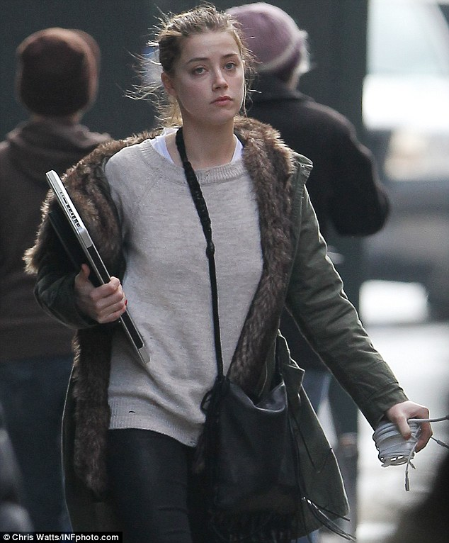 Rolled out of bed? Amber wore her hair tied back in a messy bun and looked sloppy and dishevelled in her oversized sweater and leggings