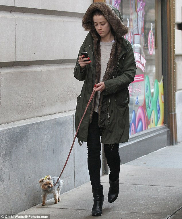 Oblivious: The 26-year-old star kept her eyes glued to her smartphone