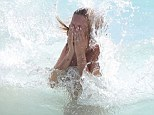 Picture perfect: Kate looked superb as she was hit by a wave in the crystal clear blue waters