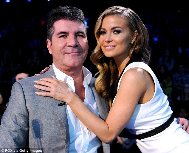 Mo wonder he's smiling! Simon Cowell gets a hug from Carmen Electra as he films The X Factor on December 12 in Hollywood