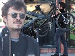 Macho man: Orlando Bloom carries his bike to the repair shop as wife Miranda Kerr confirms they'll spend Christmas together