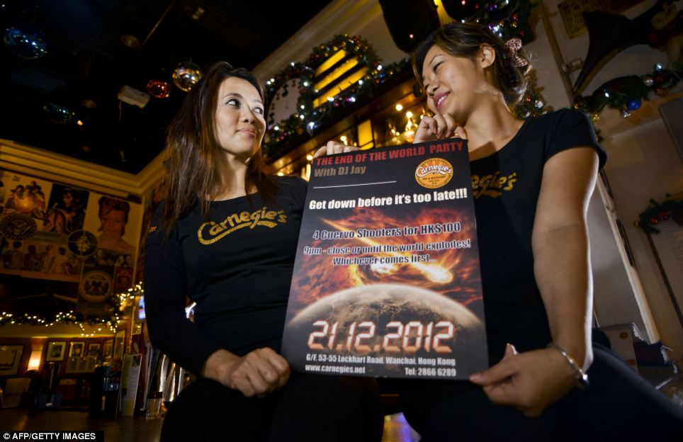Opportunity: Staff of the bar Carnegie's, pose as they hold a flyer for the 'end of the world' party, in Hong Kong