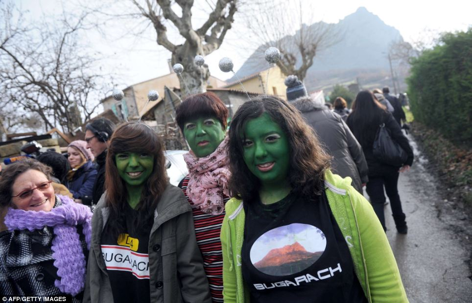 Alien fun: Women with their faces painted in green walk in the French southwestern village of Bugarach, near the 1,231 meter high peak of Bugarach - one of the few places on Earth some believe would be spared