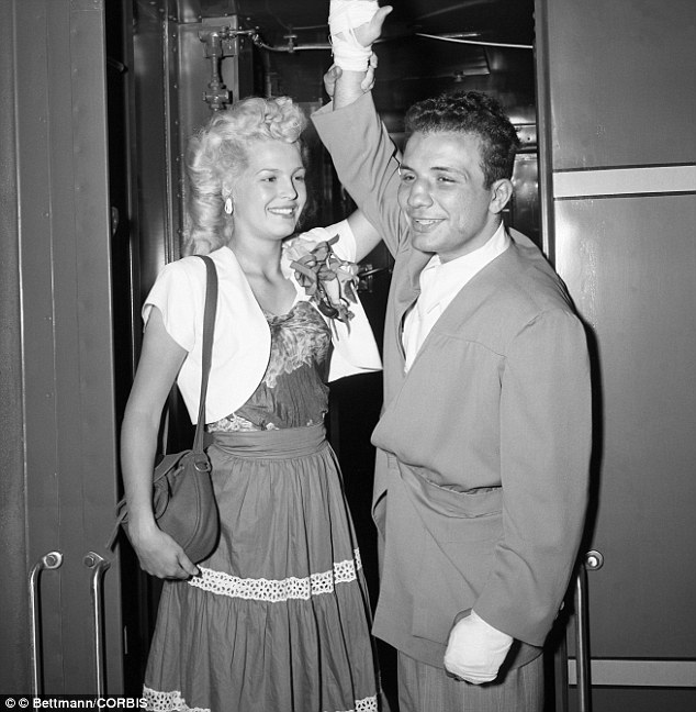 New world middleweight champion Jake La Motta has his arm raised in a symbol of victory by his wife, Vickie, as they arrive at Grand Central Station from Detroit in 1949