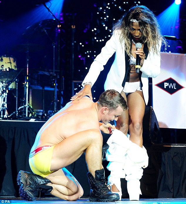 Helping hand: The singer was helped out of her suit by one of her scantily clad dancers
