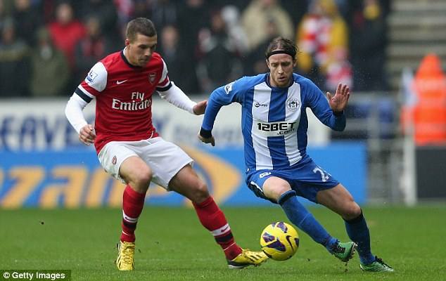 Eyes on the ball: Lukas Podolski competes with Ronnie Stam