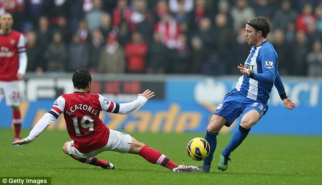 Flying in: Santi Cazorla challenges Ronnie Stam at the DW Stadium