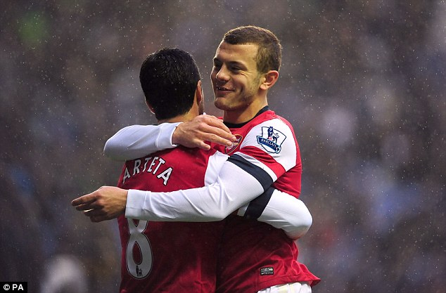 All smiles: Arteta is congratulated by Jack Wilshere after his goal