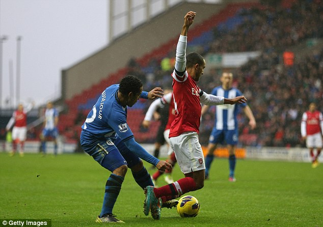 Going down: Jean Beausejour brings down Theo Walcott in the area