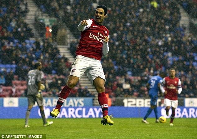 Singing in the rain: Arsenal's Mikel Arteta celebrates scoring from the penalty