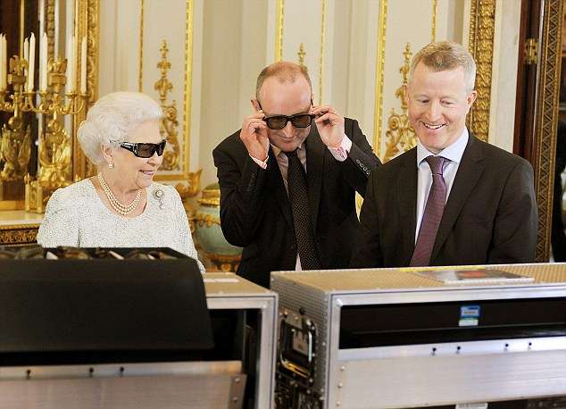 Queen of cool: Her Majesty tries on a pair of 3D glasses this year as she watches her first Christmas message to be filmed in the format