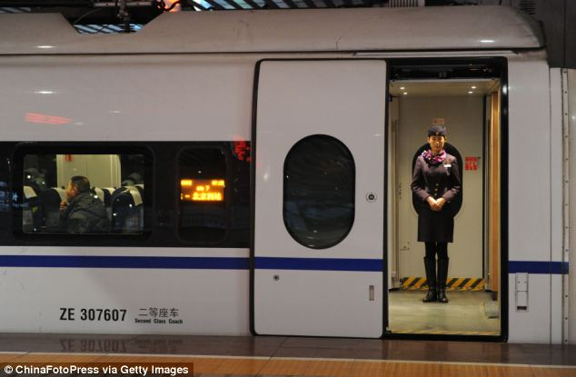 Greeting: A stewardess waits to greet passengers at a doorway of a high-speed train at Changsha South Railway Station