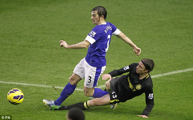 Ground force: Ronnie Stam slides in to challenge Everton full-back Leighton Baines