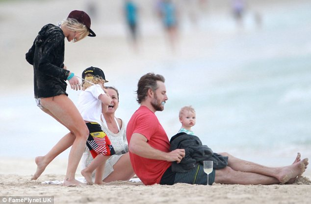 Riot: Three generations of Simpson laugh together on the sandy shores of Hawaii