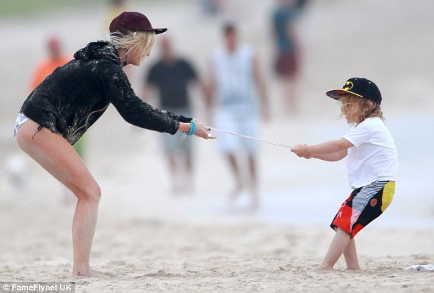 Tug of war: Mum and son see who's stronger in a battle on the sand