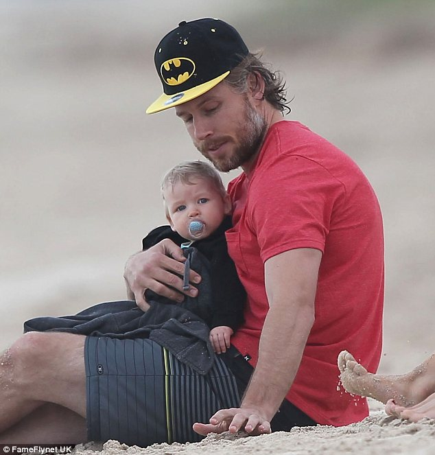 Daddy duty: Eric Johnson kept his newborn daughter close as Maxwell watched her cousin and auntie play