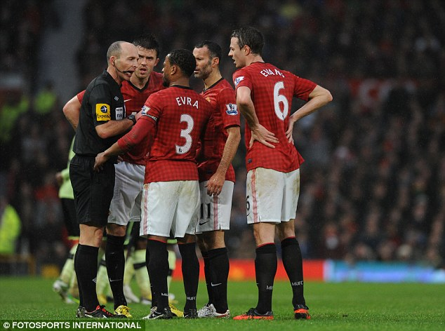 Surrounded: Manchester United players Michael Carrick, Ryan Giggs, Jonny Evans and Patrice Evra confront Mike Dean