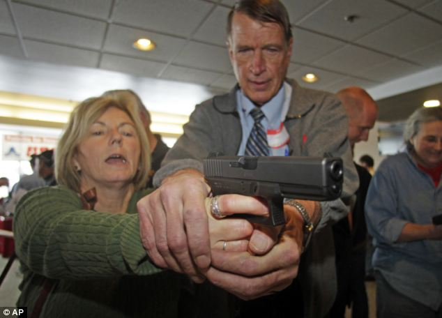 Christine Caldwell, left, receives firearms training with a 9mm Glock from Mr McCarthy. It is the latest effort to arm teachers to confront school assailants